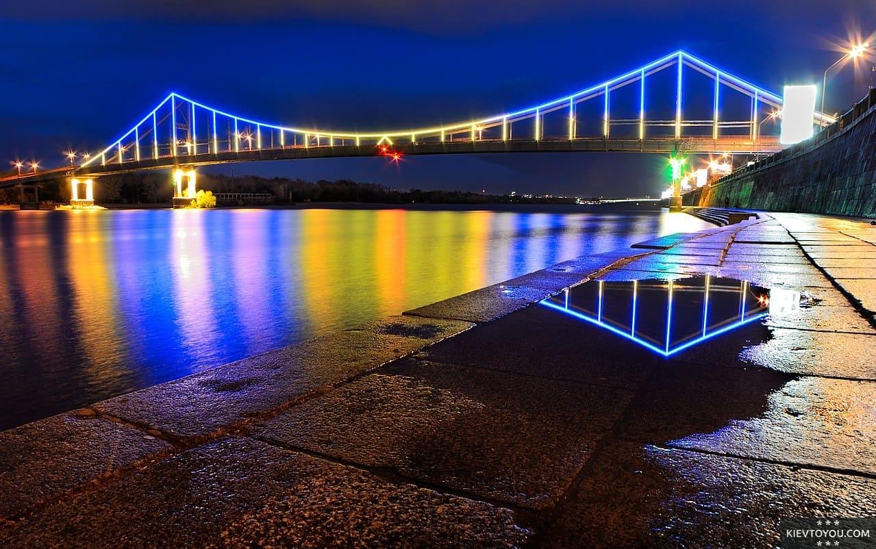Светящийся пешеходный мост в Киеве вечером
